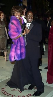 Whitney Houston added a popping item to her Post-Oscar outfit by wearing a purple fur shawl on top of her black gown.