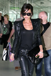 Victoria Beckham's cool black leather jacket with matching leather pants looked something fierce as she strode through Heathrow airport.