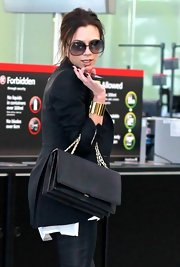 Victoria Beckham may have looked ultra casual at Heathrow Airport, but she did incorporate a touch of glamour with a shiny gold cuff bracelet.