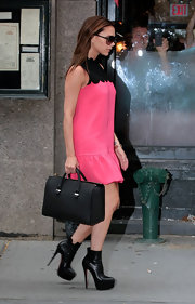 Victoria Beckham wore a pair of mile-high ankle boots while out and about in NYC. In her black and pink babydoll dress she was all leg.