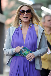 "Another day on the stylish set of ""Sex and the City"" and Kim Cattrall looked very stylish in her violet jersey knot dress. She topped her look off with a colorful pair of chandelier earrings."
