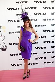 Rebecca is a purple princess in a one-shoulder cocktail dress and fantastic hat.