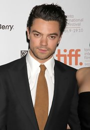 Dominic Cooper's straight hair is kept short and slicked back.