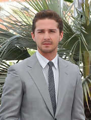 Shia adds visual interest to a basic gray suit with a narrow black and white striped tie.