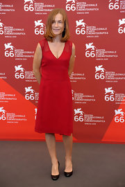 Isabelle Huppert's mesh-panel red dress was a bright pop of color at the 'White Material' photocall.