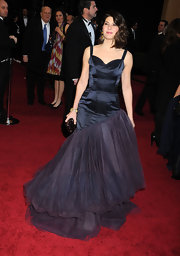 Marisa Tomei wowed at the Oscars carrying a Kotur hard case clutch that played up the plum hue of her gown.