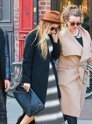 Amber Heard teamed a black leather shoulder bag with a coat and a print dress for a day out in New York City.