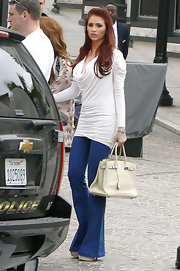 Amy Childs was spotted filming her reality show in a ruched white cowl neck top and flared trouser jeans.