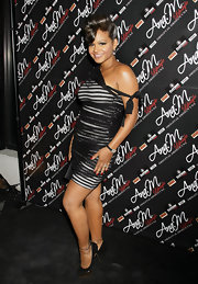 Christina wore a striped, asymmetrical mini dress with gold platformed pumps featuring a delicate, buckled ankle strap.