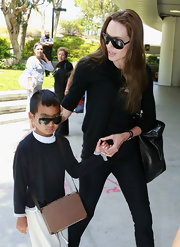 Maddox Jolie-Pitt looked cool in his designer shield sunglasses as he arrived at LAX with mom Angelina.