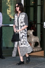 Anne Hathaway departed her NYC hotel wearing a stylish black-and-white mixed-print dress.