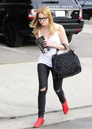 Ashley Benson toted this leather handbag with floral cutout design while out in Hollywood.