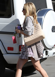 Ashley Tisdale accessorized a feminine floral dress with a structured cream quilted tote.