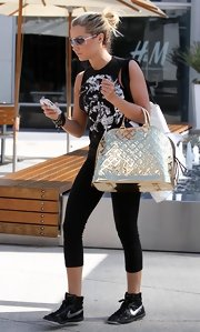 A sporty looking Miss Tisdale carried a metallic gold bowler bag while running errands. This bold handbag is a great spring accessory.
