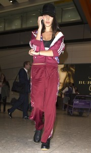 Bella Hadid arrived on a flight in London looking sporty in a burgundy track jacket by Adidas Originals x Rita Ora.