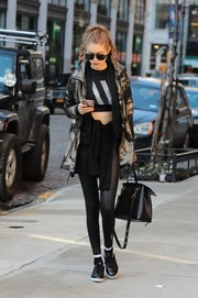 Gigi Hadid completed her sporty outfit with shiny black leggings, also by Reebok.