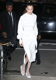 Bella Hadid styled her white look with sporty nude knee-high boots, also by DKNY.