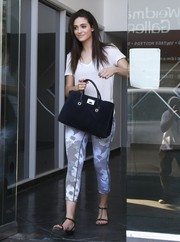 Emmy Rossum teamed her shirt with a pair of black-and-white printed leggings.