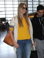 Lana Del Rey caught a flight out of LAX carrying a camel-colored leather shoulder bag.
