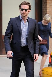 Bradley Cooper showed off his cool style while hitting an NYC hotel. His navy blue suit was super chic.