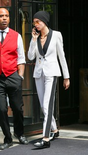 Cara Delevingne was masculine-chic in a white pantsuit with contrast lapels and side stripes while out in New York City.