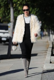 Underneath her coat, Cara Santana wore a body-con LBD layered over a striped shirt.