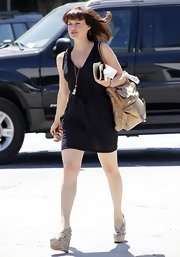 Carla paired her wedge sandals with a tan leather shoulder bag.