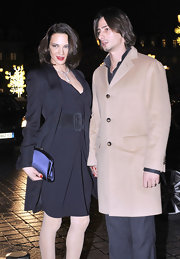 Asia Argento topped off her dress with a navy blue trench at the Armani fashion show.