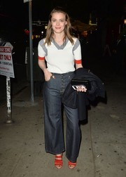 Gillian Jacobs topped off her jeans with a white V-neck knit top with gray and red accents.
