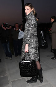 Karlie Kloss oozed classic style with this black patent leather tote and tweed coat combo at the Vivienne Westwood fashion show.