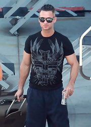 Mike wears a tight black Hustler tee for his flight to Hollywood.