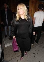 Rebel Wilson dined out at Nice Guy wearing a black satin zip-up jacket over a semi-sheer shirt.