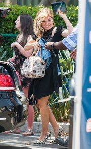 Sophia Bush had her hands full with a printed bowler bag and some clothes as she left the set of 'Extra.'