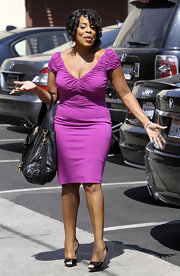 Niecy is a burst of color in a fuchsia dress with feminine ruched sleeves.