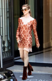 Celine Dion stepped out in Paris wearing a rust-colored lace dress with a pink underlay and bib detailing.
