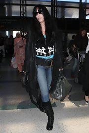 Cher complemented her cowboy-inspired outfit with a gray leather bowler bag during a flight out of LA.