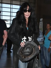 Cher was spotted at LAX wearing a Western-inspired ensemble, complete with an embellished black cowboy hat.
