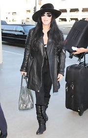 Cher looked mysterious in an all-black leather coat, boots, and hat ensemble during a flight out of LAX.