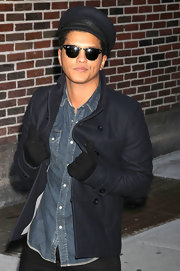 Bruno paired his navy pea coat and captains hat with round shades.