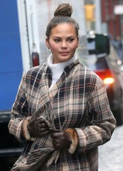 Chrissy Teigen teamed brown leather gloves with a plaid coat for a cold day out in New York City.
