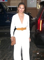 Chrissy Teigen teamed a tan suede clutch by The Row with a stylish white jumpsuit for a day out in New York City.
