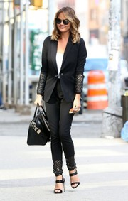 Chrissy Teigen wowed on the streets of NYC in a mesh-accented black pantsuit by Kempner.