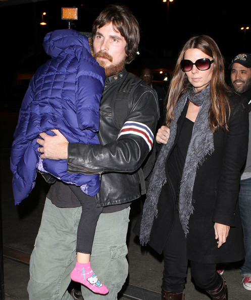 Sibi Blazic cozied up in a black wool coat and a gray scarf during a flight out of LAX.