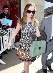 A mint leather tote bag complemented Christina's dress.
