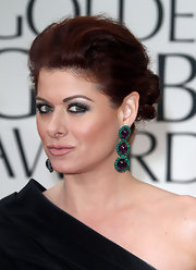 Debra Messing created a smoky-eyed look using shimmering jade green shadows and lots of black eye pencil and mascara at the 69th Annual Golden Globe Awards.