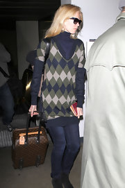 Claudia Schiffer traveled in style with a brown Louis Vuitton monogrammed suitcase in tow.