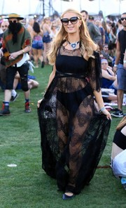 Paris Hilton put on a sultry display at Coachella in a sheer black maxi dress by Michael Costello.