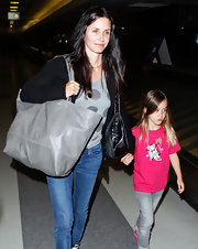 Courtney Cox headed through LAX carrying an oversize gray snakeskin tote.