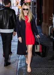 Dakota Fanning looked impeccable in a black coat layered over a red Alexander McQueen dress while out in New York City.