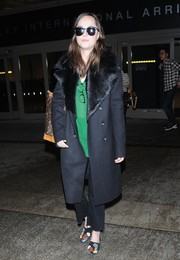 Dakota Johnson kept it comfy yet chic in embellished suede slippers by The Row during a flight to LA.